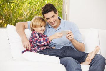 Vater und Sohn auf dem Sofa, machen Selfies