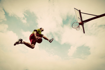 Young man making slam dunk playing streetball, basketball