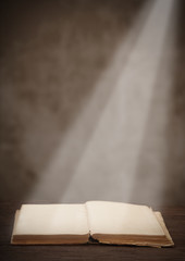 old open book on a wooden table light beam illuminates the page