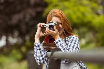 Smiling young woman taking a photo at camera
