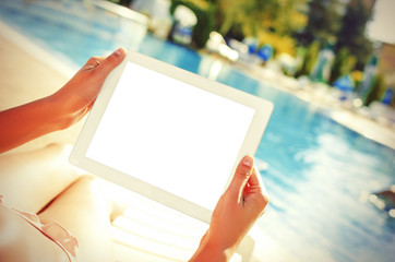 With tablet sitting at swimming pool