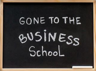 Gone to the business school message written on blackboard