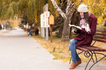 Молодая девушка осенью читает книгу в парке.