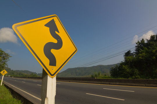 Winding road sign on blue sky