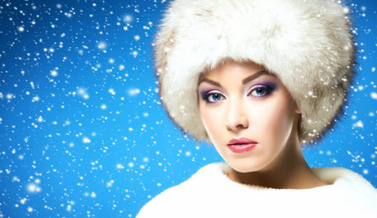 Glamour portrait of young and beautiful woman in winter hat over