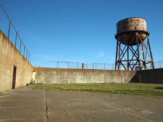 Rusting water tower stands beyond the wall  and bard wire fence