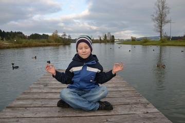 Junge beim Yoga draußen