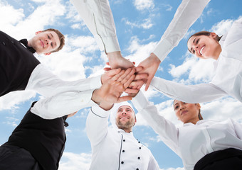 Chef And Waiters Piling Hands Against Sky