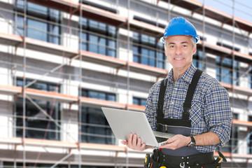 Architect Using Laptop Against Building