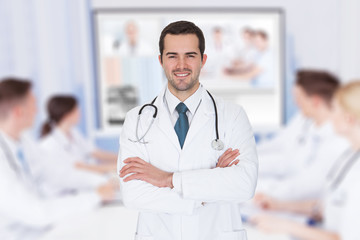 Doctor With Arms Crossed Against Team Video Conferencing