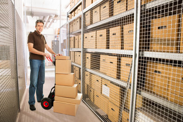 Delivery Man With Boxes On Hand truck In Warehouse