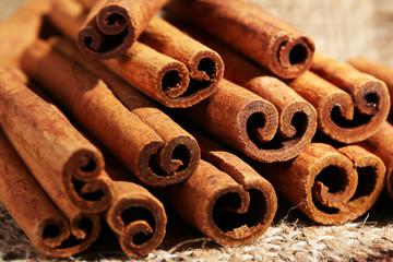Cinnamon sticks on sackcloth on table close up