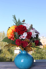 Flower bouquet in blue vase on table on natural background