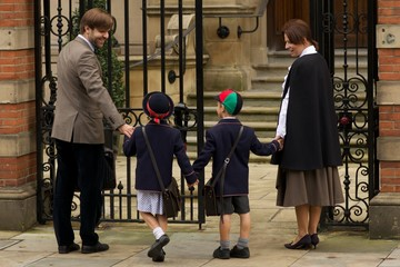 Family of four entering old school gates
