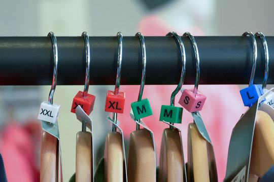 Hangers with clothes and sizes on rail