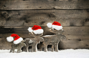 Three mooses wearing santa hats on grey wooden background
