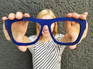 Mädchen hält Brille vor Augen