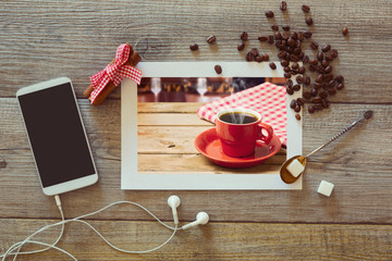 Photo of coffee cup with smart phone and beans.