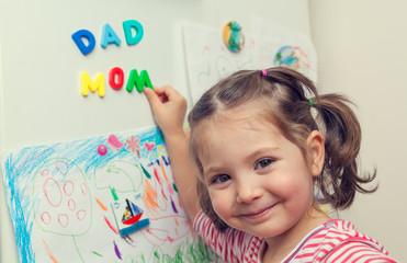 child forms mom dad words on refrigerator