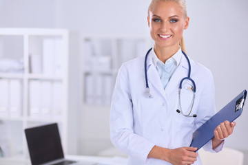 Smiling female doctor with a folder in uniform standing at