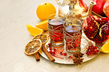 Traditional arabic tea with metal teapot pomegranate and spices
