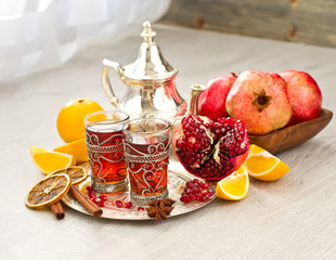 Traditional arabic tea with metal teapot and fruits