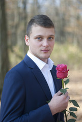 handsome young man in a suit with a rose