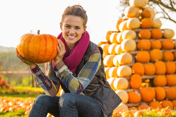 Portrait of happy young woman sitting with pumpkin
