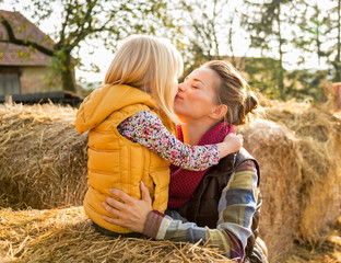Portrait of mother and child kissing while sitting on haystack