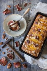 orange plumcake with pecan walnuts on mold on rustic table