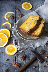 citrus cake on plate with pecan walnuts and orange slices