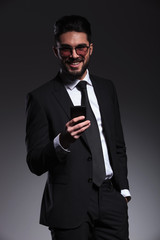 business man smiling while holding a phone