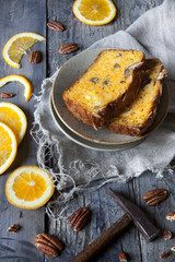two slices of citrus cake on table with hammer and orange slices