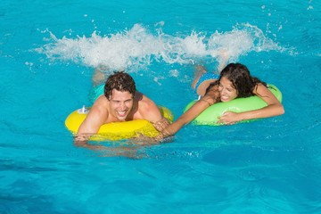 Couple in inflatable rings at swimming pool