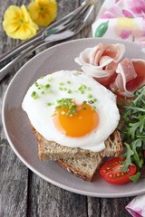 Fried egg with fresh bread,prosciutto,arugula and tomatoes