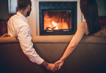 romantic couple sitting front  fireplace