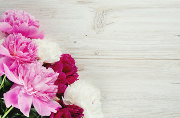 colorful peonies on white wooden surface