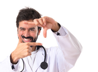Doctor focusing with his fingers on a white background