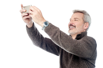 Happy aged man taking pictures of themselve