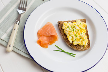 Healthy breakfast with scrambled eggs on toast and salmon
