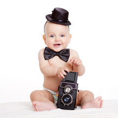 Baby boy plays with vintage camera against white background