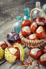brown chestnuts in basket and vials with tincture on old table