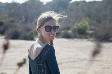Chica rubia con gafas de sol y contraluz en el pelo