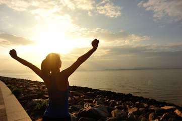 cheering woman open arms under the sunrise at seaside