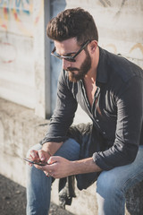 young handsome attractive bearded model man using smartphone