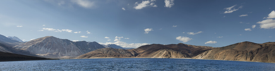Deep blue mountain lake among hills panorama
