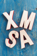 decorative wooden letters xmas on a blue background, top view