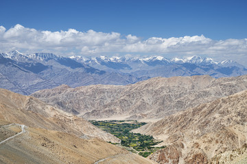 Green valley and winding road in Himalayas aerial view