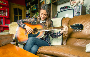 Young hipster girl playing acoustic guitar at home