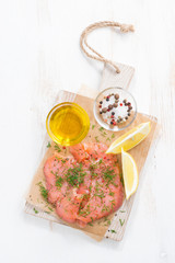 salted salmon and ingredients on a wooden board, top view
